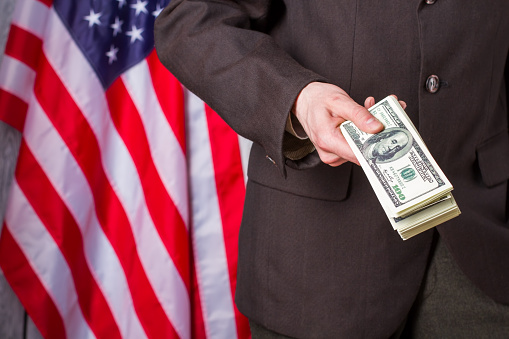 Businessman holding money beside flag.