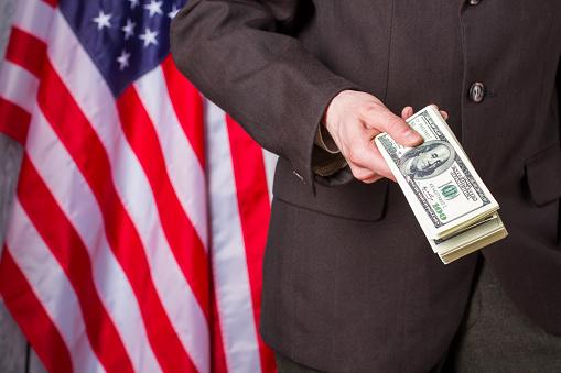 Businessman holding money beside flag.